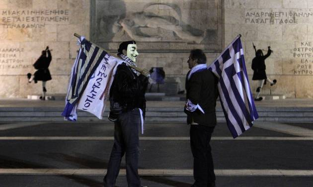 FILE - In this Sunday Nov. 11, 2012, file photo, supporters from the Independent Greeks party hold Greek flags as Presidential guards performs the changing of the guards ceremony outside the Greek parliament during an anti- austerity rally in central Athens. Stocks are opening lower on Wall Street Tuesday, Nov. 13, 2012, as a deal to rescue the Greek economy now looks much less certain than it had just one day ago. (AP Photo/Petros Giannakouris, File)