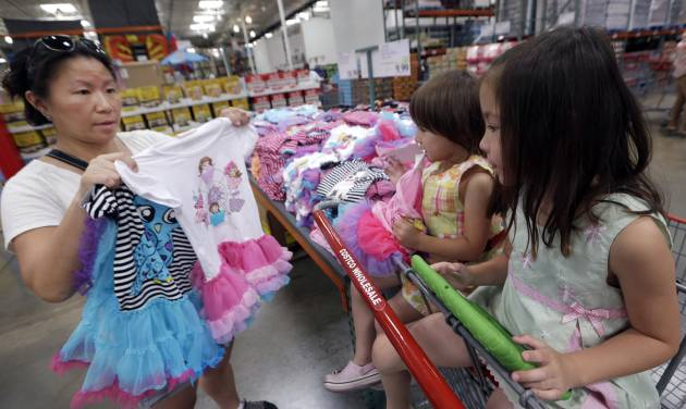 In this June 4, 2014 photo, Carry Johnson, left, shows dresses to her daughters Zoey, 3, center, and Payton while they shop at a Costco in Plano, Texas. The private Conference Board reports on consumer confidence for July on Tuesday, July 29, 2014. (AP Photo/LM Otero, File)