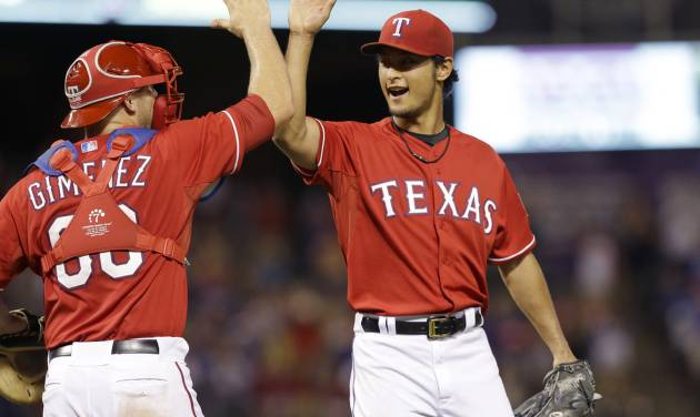 Texas Rangers starting pitcher Yu Darvish, right, of Japan, celebrates with catcher Chris Gimenez after the final out of the ninth inning of a baseball game against the Miami Marlins in Arlington, Texas, Wednesday, June 11, 2014. The Rangers won 6-0. (AP Photo/LM Otero)