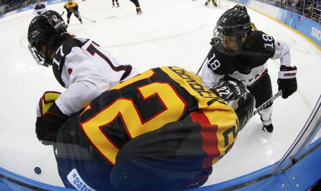 Yuka Hirano (17) and Tomoko Sakagami (18) of Japan battle up against the boards with Kerstin Spielberger of Germany during the 2014 Winter Olympics women's ice hockey game at Shayba Arena, Thursday, Feb. 13, 2014, in Sochi, Russia. (AP Photo/Petr David Josek)