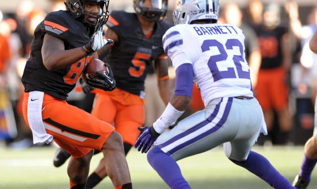 Oklahoma State wide receiver Tracy Moore, left, holds up his hand to fend off Kansas State's Tre Flowers, right, during the second half of an NCAA football game in Stillwater, Okla., Saturday, Oct. 5, 2013. (AP Photo/Brody Schmidt)