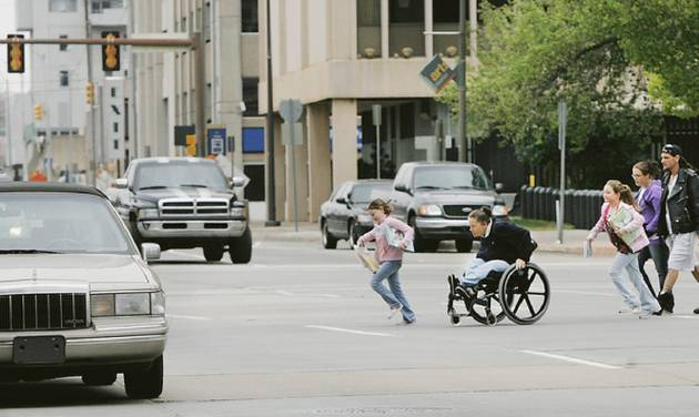 A woman in a wheelchair and children hurry to cross Hudson Avenue between the Oklahoma County Courthouse and City Hall on Thursday. The six-lane street with 12-foot-wide lanes — highway standard — gets the worst grade from consultant Jeff Speck on walkability.  Photo By Jim Beckel, The Oklahoman