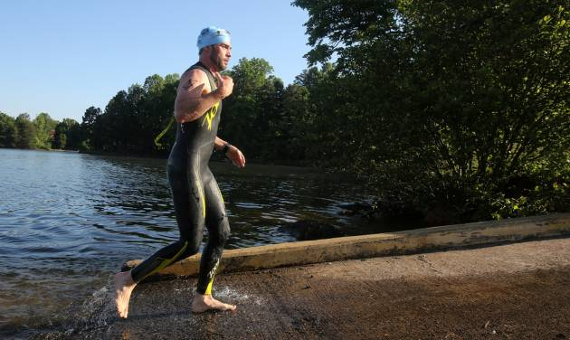 Six-time NASCAR champion driver Jimmie Johnson finishes the swim portion of the Over the Mountain Triathlon in Kings Mountain, N.C., Saturday, May 17, 2014.  (AP Photo/The Star, Ben Earp)