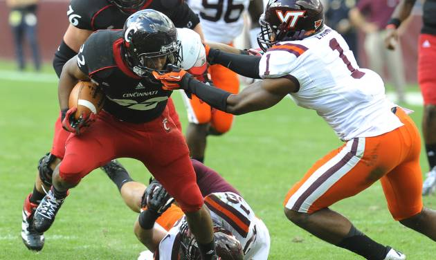 Cincinnati running back George Winn has his face mask grabbed by Virginia Tech cornerback Antone Exum (1) during the first half of an NCAA college football game, Saturday, Sept. 29, 2012, in Landover, Md. (AP Photo/Richard A. Lipski)
