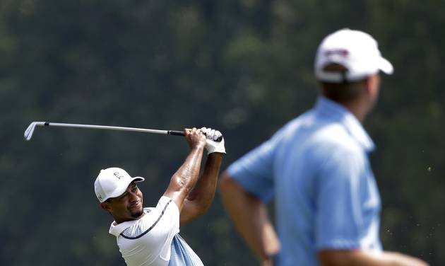 Tiger Woods hits from the fairway on the second hole as Steve Stricker looks on during a practice round for the PGA Championship golf tournament at Valhalla Golf Club on Wednesday, Aug. 6, 2014, in Louisville, Ky. The tournament is set to begin on Thursday. (AP Photo/David J. Phillip)