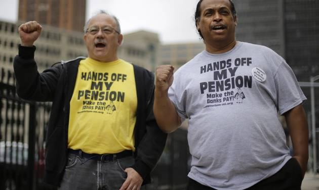 FILE - In a Thursday, July 3, 2014 file photo, Detroit retirees Mike Shane, left, and William Davis protest near the federal courthouse in Detroit. Workers and retirees approved pension cuts in Detroit's bankruptcy by a landslide, the city reported Monday, a crucial step to emerging from the largest municipal insolvency in U.S. history. The city disclosed results from two months of balloting, which ended July 11. Judge Steven Rhodes still must hold a trial in August to determine if Detroit's overall bankruptcy plan is fair and feasible to all creditors, from Wall Street to Main Street, but support from retirees is vital. (AP Photo/Paul Sancya, File)
