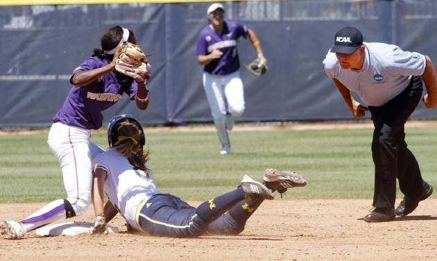 Washington Huskies short stop Jenni McNeill tags Michigan baserunner Ashley Lane out as she slides into second during the Women's College World Series elimination game versus Michigan. The Washington Huskies would won 4-1 on June 2, 2013. Photo by KT KING, The Oklahoman
