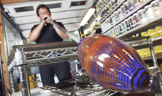 Glasswork designer Chris McGahan blows into a piece of hot glass at his studio. McGahan's work is on display in his pizza restaurant in Yukon. photo BY STEVE GOOCH, THE OKLAHOMAN