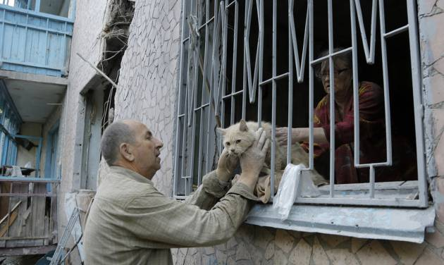 Valery who gave only his first name takes his suffered cat from his damaged house after shelling in the city of Slovyansk, Donetsk Region, eastern Ukraine Monday, June 30, 2014. Residential areas came under shelling on Monday morning from government forces. (AP Photo/Dmitry Lovetsky)