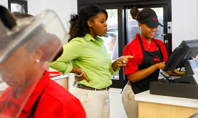 In this July 31, 2014 photo, Quamisha Nelson, owner and operator of the Smoothie King in Jacksonville, N.C., center, works alongside Latasia White, 15, as she rings up a customer's order at the drive-thru. The government reports on state unemployment rates for July on Monday, Aug. 18, 2014. (AP Photo/The Jacksonville Daily News, John Sudbrink)