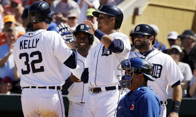 Detroit Tigers left fielder Don Kelly (32) is greeted at home plate by scoring teammates Austin Jackson, back center, Victor Martinez and Alex Avila, right, after his grand slam during the fifth inning of a spring exhibition baseball game against the Toronto Blue Jays in Lakeland, Fla., Tuesday, March 18, 2014. (AP Photo/Carlos Osorio)
