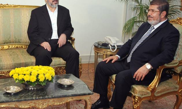 In this image provided by the Egyptian President, Hamas leader Khaled Mashaal, left, meets with Egyptian President Mohammed Morsi at the Presidential Palace in Cairo, Sunday, Nov. 18, 2012. About 500 Egyptian activists have crossed into Gaza to deliver medical supplies and show support for Palestinians facing an Israeli offensive. Morsi, comes from the Muslim Brotherhood, the parent group of Hamas and has met with Hamas leaders in Cairo. (AP Photo/Egyptian Presidency)
