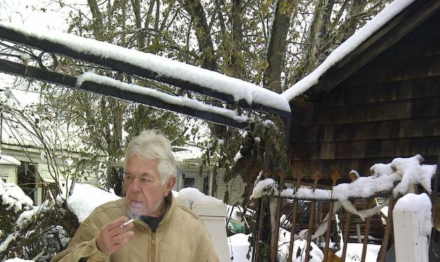 """Vladimir Repnin, 63, emerges from his powerless home with snow shovel in hand and a cigarette, Thursday, Nov. 8, 2012, in New Dorp Beach, in the Staten Island borough of New York. Reflecting his isolation from the outside world he asked; """"Who won? Obama?"""" (AP Photo/Tom Hays)"""