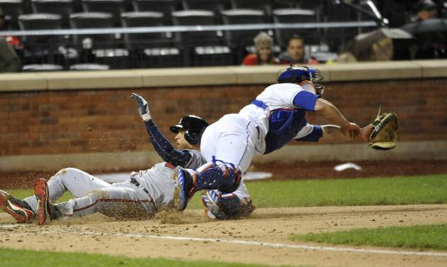 Atlanta Braves' Andrelton Simmons, left, scores at home plate as New York Mets catcher Anthony Recker misses ball in the fifth inning of the second baseball game at Citi Field, Saturday, May 25, 2013, in New York. (AP Photo/Kathy Kmonicek)