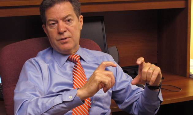 Kansas Gov. Sam Brownback answers questions for reporters during an impromptu visit to The Associated Press office at the Statehouse, Wednesday, July 23, 2014, in Topeka, Kan. Brownback called on wind-energy advocates and opponents of a renewable-energy rule to compromise on the policy's future. (AP Photo/Credit withheld)