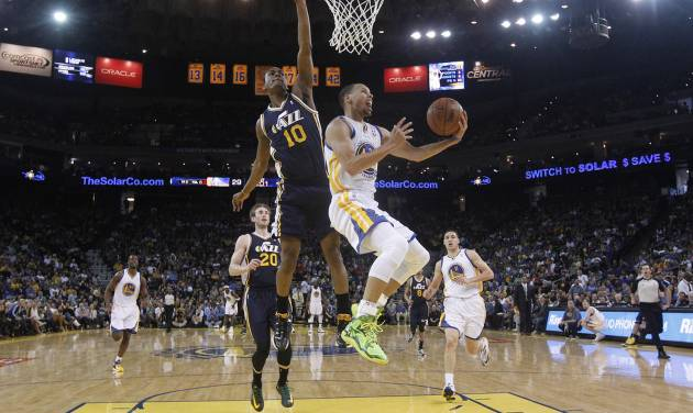 Golden State Warriors guard Stephen Curry, center left, drives to the basket as Utah Jazz guard Alec Burks (10) defends during the first half of an NBA basketball game Sunday, April 6, 2014, in Oakland, Calif. (AP Photo/Marcio Jose Sanchez)