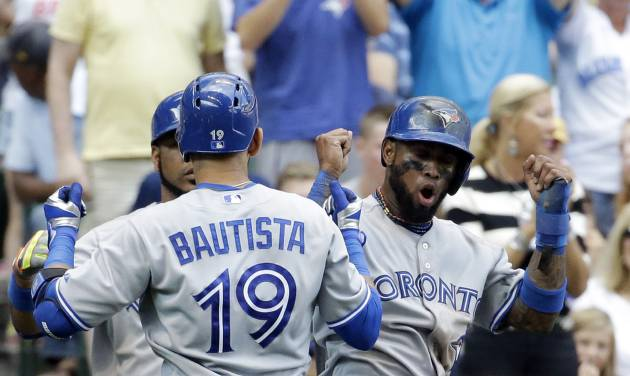 Toronto Blue Jays' Jose Bautista (19) celebrates hiS three-run home run with teammate Jose Reyes during the sixth inning of a baseball game against the Milwaukee Brewers Wednesday, Aug. 20, 2014, in Milwaukee. (AP Photo/Morry Gash)