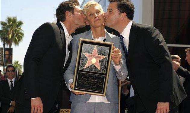 Talk show host and comedian Ellen DeGeneres, center, is kissed by Ryan Seacrest, left, and Jimmy Kimmel at her Hollywood Walk of Fame star ceremony on Tuesday, Sept. 4, 2012, in Los Angeles. (Photo by Chris Pizzello/Invision/AP)