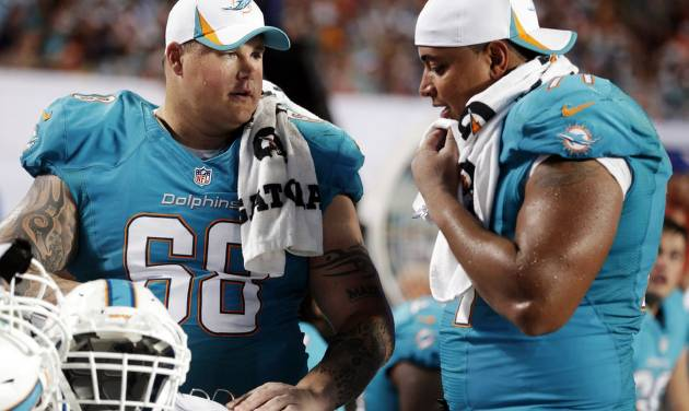 FILE - In this Aug. 24, 2013, file photo, Miami Dolphins guard Richie Incognito (68) and tackle Jonathan Martin (71) look over plays during an NFL preseason football game against the Tampa Bay Buccaneers in Miami Gardens, Fla. A report is expected soon from the NFL investigation into the Dolphins' harassment scandal involving Martin and Incognito. The Dolphins don't expect any major revelations, but neither player is likely to be back with the team next season.  (AP Photo/Wilfredo Lee, File)
