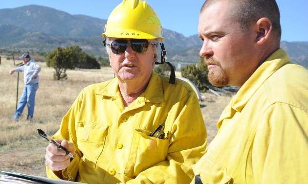 Wetmore volunteer firemen Greg Tabuteau, left, and Dee Murphy discuss strategy for fighting a wildfire Thursday, Oct 24, 2012 in Wetmore, Colo. The fire started Wednesday afternoon near Tabuteau's home just west of Wetmoreand damaged at least 14 residences in the rural area. (AP Photo/Pueblo Chieftain, Chris McLean)