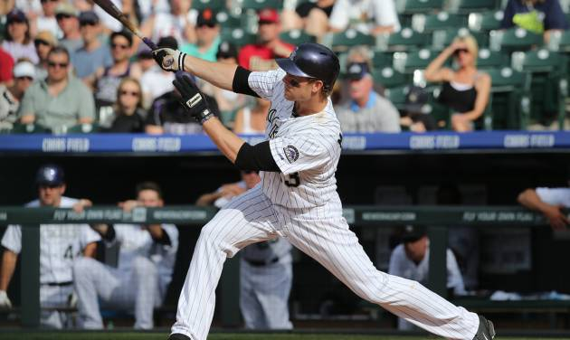 Colorado Rockies' Justin Morneau follows the flight of his solo home run against the New York Mets in the ninth inning of the Mets' 5-1 victory in a baseball game in Denver, Sunday, May 4, 2014. (AP Photo/David Zalubowski)