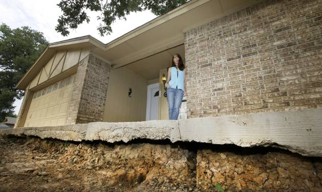 Barbara Brown poses for a photo on the front step of her home that now sits about one foot off the surface of her lawn, Saturday, June 21, 2014, in Reno, Texas. Brown said that the top of the step once sat about four inches off the surface of her lawn. Brown said she believes the sinkholes on her property and the drop of her lawn have to do with natural gas drilling. (AP Photo/Tony Gutierrez)