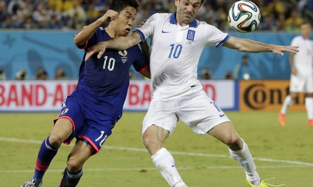 Greece's Giorgos Karagounis, right, struggles with Japan's Shinji Kagawa to get to the ball during the group C World Cup soccer match between Japan and Greece at the Arena das Dunas in Natal, Brazil, Thursday, June 19, 2014.  (AP Photo/Petr David Josek)