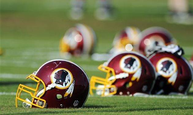 """FILE - In this June 17, 2014, file photo, Washington Redskins helmets sit on the field during an NFL football minicamp in Ashburn, Va. The U.S. Patent Office ruled Wednesday, June 18, 2014, that the Washington Redskins nickname is """"disparaging of Native Americans"""" and that the team's federal trademarks for the name must be canceled. The ruling comes after a campaign to change the name has gained momentum over the past year. (AP Photo/Nick Wass, File)"""