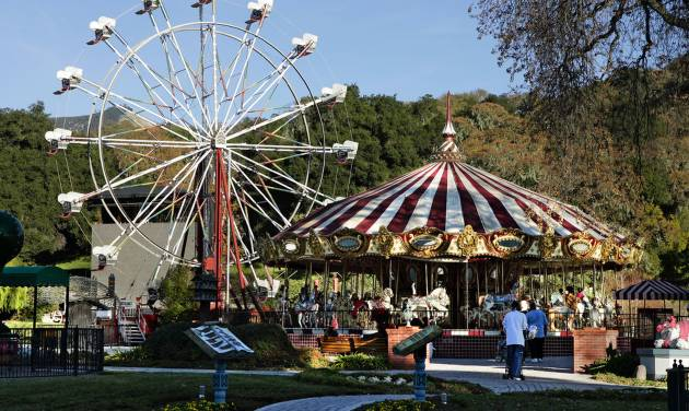 FILE - This Dec. 17, 2004 file photo shows a carousel, right, and ferris wheel, left, on the property at pop star Michael Jackson's Neverland Ranch home, in Santa Ynez, Calif., where several hundred children were invited to the estate for a holiday celebration. In 2014, Jackson's playtime palace sits empty now. The backyard circus and laughter of children are long gone, but the house and its fanciful memories live on. (AP Photo/Mark J. Terrill, file)