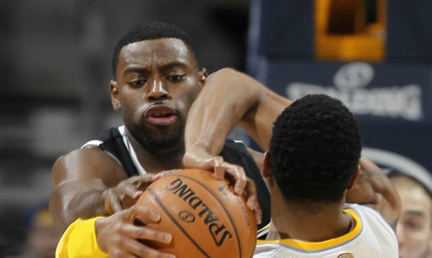 Sacramento Kings guard Tyreke Evans, left, tries to steal the ball from Denver Nuggets guard Andre Iguodala during the first quarter of an NBA basketball game in Denver on Saturday, Jan. 26, 2013. (AP Photo/David Zalubowski)