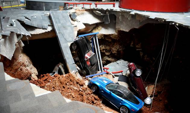 In this Wednesday, Feb. 12, 2014 photo, cars lie in a sinkhole that opened up at the Skydome showroom in the National Corvette Museum in Bowling Green, Ky. The sinkhole that swallowed eight cars at the has become such an attraction that officials want to preserve it. They may even put one or two of the cars back inside the hole. The board of the museum in Kentucky voted Wednesday, June 25, 2014 to preserve a large section of the sinkhole that opened beneath the museum in February. (AP Photo/Michael Noble Jr.)