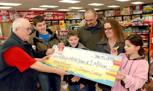 The Gunn family of Wolf Creek, Ore., accepts a symbolic check for $1 million before taxes from Oregon Lottery official Ray Martin on Tuesday, Jan. 15, 2013, at the convenience store where they bought it in Merlin, Ore. Riley Gunn lost his job as a project manager for a telecommunications company in May 2012 and moved his family to a one-room cabin outside Wolf Creek, Ore. While he and his wife were driving home, they pulled off the freeway for corn dogs and pizza pockets and bought an $8 ticket, and won $1 million dollars. Riley and Misti Gunn are at center, with their sons Elijah, 13, left, and Isac, 11, and daughter, Destenie, 9, right. (AP Photo/Jeff Barnard)