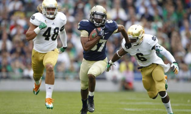 Navy's Shawn Lynch, centre, tries to get past Notre Dame's Theo Riddick, right, during their NCAA college football game in Dublin, Ireland, Saturday, Sept. 1, 2012. (AP Photo/Peter Morrison)
