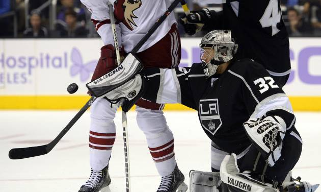 Phoenix Coyotes left wing David Moss, left, tries to get a shot in against Los Angeles Kings goalie Jonathan Quick, right, as defenseman Robyn Regehr helps defend during the first period of their NHL hockey game on Thursday, Oct. 24, 2013, in Los Angeles. (AP Photo/Mark J. Terrill)