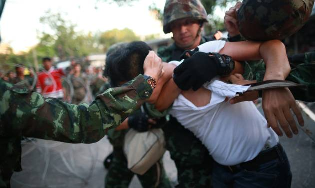 """A protester is detained by Thai soldiers during an anti-coup demonstration at the Victory Monument in Bangkok, Thailand, Saturday, May 24, 2014. Thailand's coup leaders said Saturday that they would keep former Prime Minister Yingluck Shinawatra, Cabinet members and anti-government protest leaders detained for up to a week to give them """"time to think"""" and to keep the country calm. They also summoned outspoken academics to report to the junta. (AP Photo/Wason Wanichakorn)"""