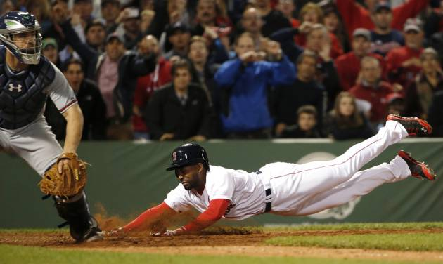 Boston Red Sox's Jackie Bradley Jr. dives home with the game-winning run on an infield single by teammate Xander Bogaerts as catcher Evan Gattis, left,  looks on during the ninth inning of their 4-3 win in a baseball game at Fenway Park, Thursday, May 29, 2014, in Boston. (AP Photo/Winslow Townson)