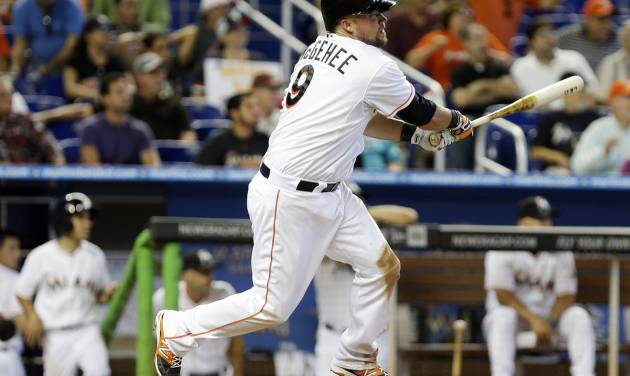 Miami Marlins' Casey McGehee hits a single to score Jeff Baker and Giancarlo Stanton in the eighth inning of a baseball game against the Colorado Rockies, Thursday, April 3, 2014, in Miami. The Marlins won 8-5. (AP Photo/Lynne Sladky)