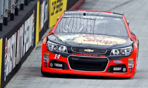 Driver Jeff Burton (14) drives down the back straight during practice for the Irwin Tools Night Race NASCAR Sprint Cup Series auto race at Bristol Motor Speedway on Friday, Aug. 22, 2014, in Bristol, Tenn. (AP Photo/Wade Payne)