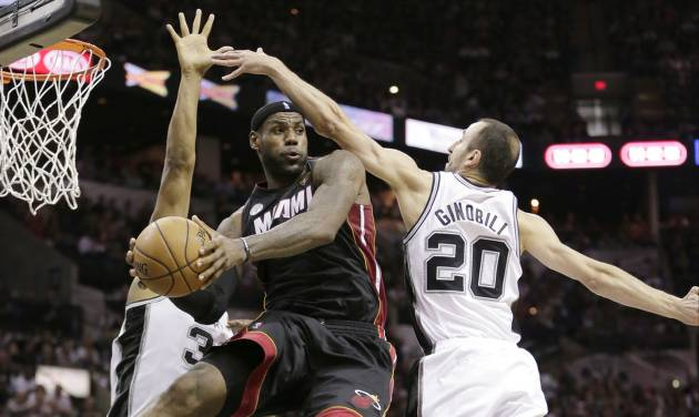 FILE - In this June 13, 2013 file photo, Miami Heat's LeBron James (6) passes between San Antonio Spurs' Boris Diaw (33), of France,  and Manu Ginobili (20), of Argentina, during the second half at Game 4 of the NBA Finals, in San Antonio.  A rematch of last year's thrilling NBA Finals finish is possible, but the Spurs and Heat would have to get through tough paths to get there. (AP Photo/Eric Gay, File)