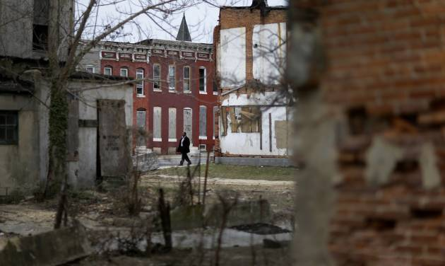 In this April 4, 2013 picture, a man walks past boarded up row houses and vacant lots in Baltimore. Baltimore has lost nearly a third of its population since it peaked in the 1950s, and today an estimated 16,000 buildings are vacant or abandoned. (AP Photo/Patrick Semansky)