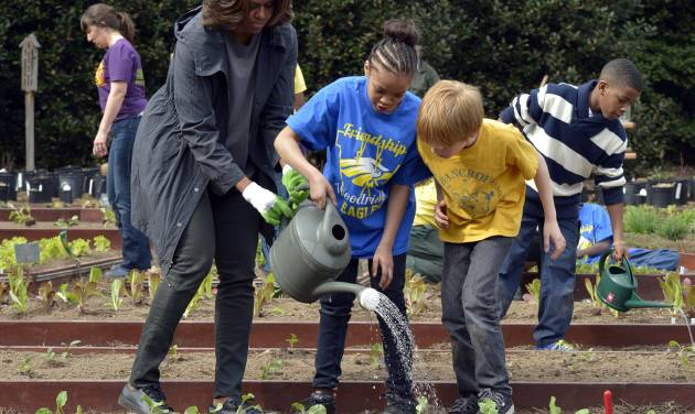 FILE - This April 2, 2014 file photo shows first lady Michelle Obama helping to hold a watering can after she and Friendship Public Charter Elementary School student Dynasty Meade, center, and Bancroft Elementary School student Silas Stutz, right, planted broccoli in the White House Kitchen Garden at the White House in Washington. The White House says tours of Michelle Obama's produce garden will be operating again soon. The tours were grounded after mandatory budget cuts went into effect last year. Public tours of parts of the White House also were halted due to the cuts but resumed after President Barack Obama signed legislation funding government operations. The garden tours are scheduled to resume the week of July 14. They are open to community and school groups that are interested in gardening and healthy eating. (AP Photo/Susan Walsh, File)