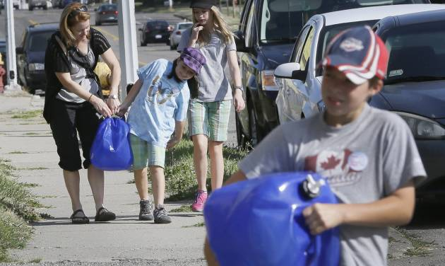 Mary Ellen Kavanaugh, and her children Abby, second from left, Grace and Owen, right, of Windsor, help carry water jugs to St. Peter's Episcopal Church in Detroit, Thursday, July 24, 2014, for a water station being set up to help Detroit residents who need water. A small group of Canadians brought 1,000 liters (264 gallons) of water from Windsor, Ontario, to Detroit to protest thousands of residential service shutoffs by Detroit's water department. (AP Photo)