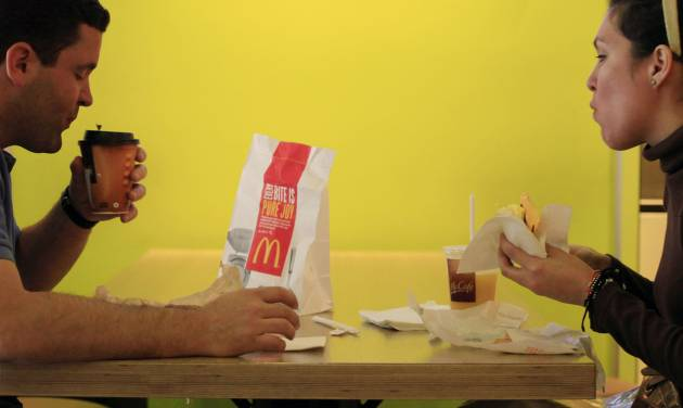 FILE- In this Wednesday, Sept. 12, 2012, file photo, Carlos Gonzalez and Elsa Guzman eat breakfast at a McDonald's restaurant, in New York. The world's biggest hamburger chain said Thursday, Nov. 8, 2012, that a key sales figure fell for the first time in nearly a decade in October, as it faced the double whammy of a challenging economy abroad and intensifying competition at home. (AP Photo/Mark Lenniha, File)