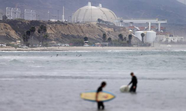 FILE - In this Friday, June 7, 2013 file photo, surfers pass in front of the San Onofre nuclear power plant in San Onofre, Calif. A $2.3 billion proposal to rewire portions of Southern California's transmission grid following the closure of the San Onofre nuclear power plant could mean higher power bills for consumers.  (AP Photo/Gregory Bull, File)