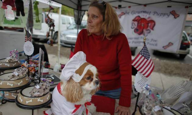 "Cynthia Kopp and her dog Aires wait for customers at a farmers market, Saturday Oct. 6, 2012, in Doylestown Pa. Kopp, 56, lost her accounting job in the recession and now works part-time as a supermarket cashier and comes to the farmers market each week to sell $5 bags of her gourmet dog biscuits. ""If Aries could vote he would vote for Romney,"" Kopp said. ""Because mommy needs a job and she thinks Romney is the only candidate that could help get her one.""(AP Photo/ Joseph Kaczmarek)"