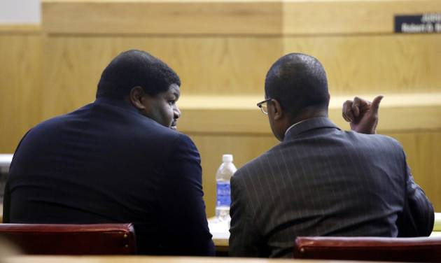 Former Dallas Cowboy NFL football player Josh Brent talks with a member of is defense team, right,  during his trial for intoxication manslaughter, Friday, Jan. 17, 2014, in Dallas. Brent is accused of driving drunk at the time of a December 2012 crash that killed Cowboys practice squad player Jerry Brown. (AP Photo/Tony Gutierrez)