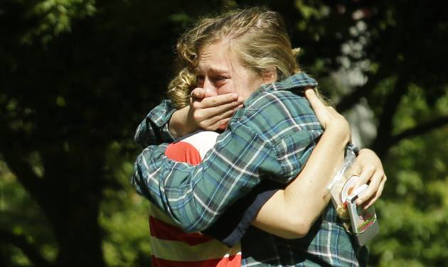 Two women embrace near a prayer circle on the campus of Seattle Pacific University, Friday, June 6, 2014 in Seattle. Classes were canceled Friday following a shooting at Otto Miller Hall Thursday afternoon. A 19-year-old man was fatally shot and two other young people were wounded after a gunman entered the foyer  and started shooting.  Aaron R. Ybarra, 26, was booked into the King County Jail late Thursday for investigation of homicide, according to police and the jail roster. (AP Photo/Ted S. Warren)