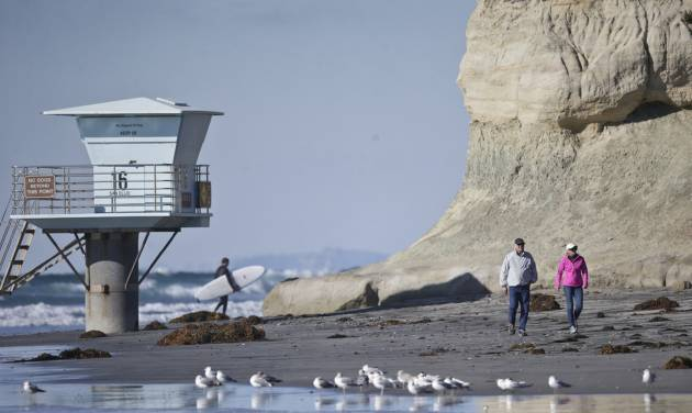 A couple walks along the beach as a surfer leaves the water on a sunny but cold day Wednesday, Dec. 16, 2015, in Cardiff, Calif.  (AP Photo/Lenny Ignelzi)