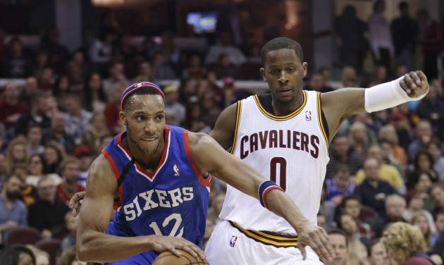 Philadelphia 76ers' Evan Turner (12) drives past Cleveland Cavaliers' C.J. Miles (0) during the first quarter of an NBA basketball game Saturday, Nov. 9, 2013, in Cleveland. (AP Photo/Tony Dejak)