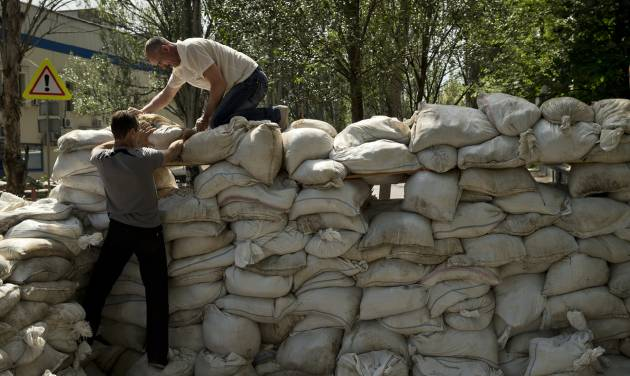 People pile up sand bags to set up a shooting position on the road leading from the airport to Donetsk, Ukraine, Tuesday, May 27, 2014. The eastern city of Donetsk was in turmoil Tuesday a day after government forces used fighter jets to stop pro-Russia separatists from taking over the airport. The mayor said 40 people were killed and went on television to urge residents to stay at home.(AP Photo/Vadim Ghirda)